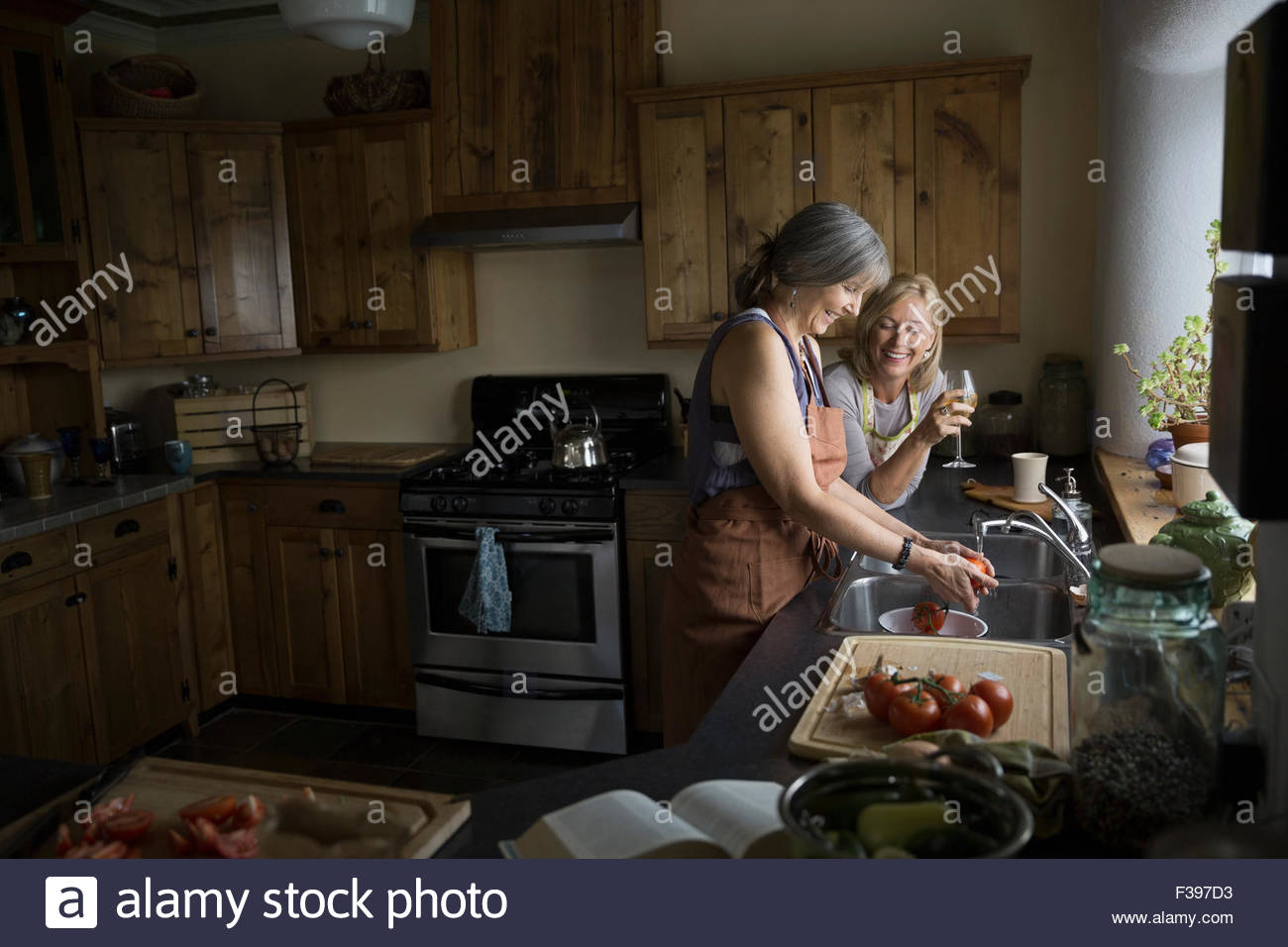 Women cooking and drinking wine in kitchen - Stock Image