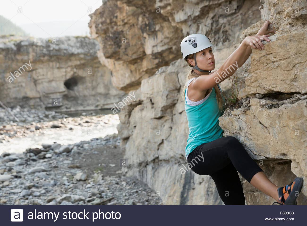 Female rock climber climbing rock formation - Stock Image