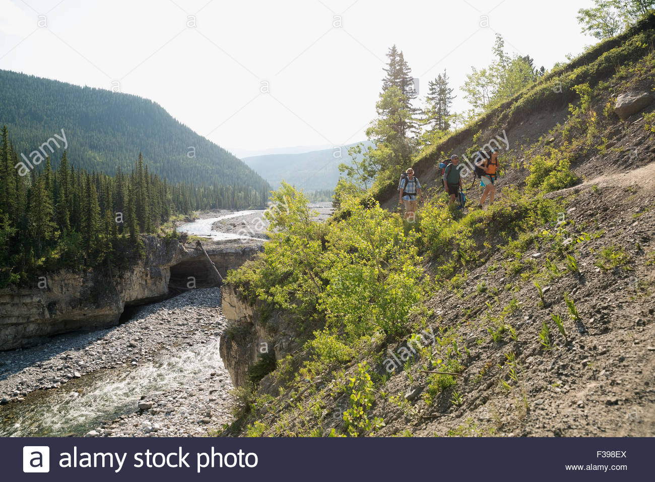 Friends hiking along craggy ridge above river - Stock Image