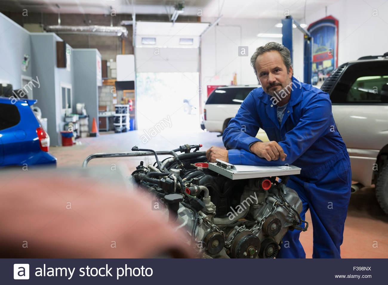 Portrait confident mechanic at engine auto repair shop - Stock Image