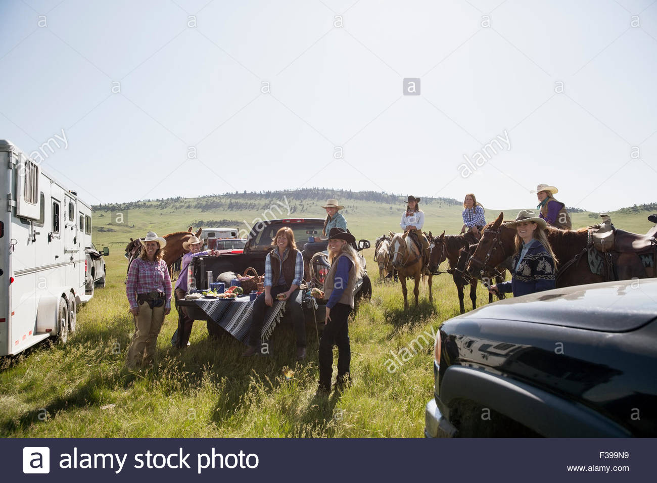 Female ranchers gathering for picnic around truck - Stock Image