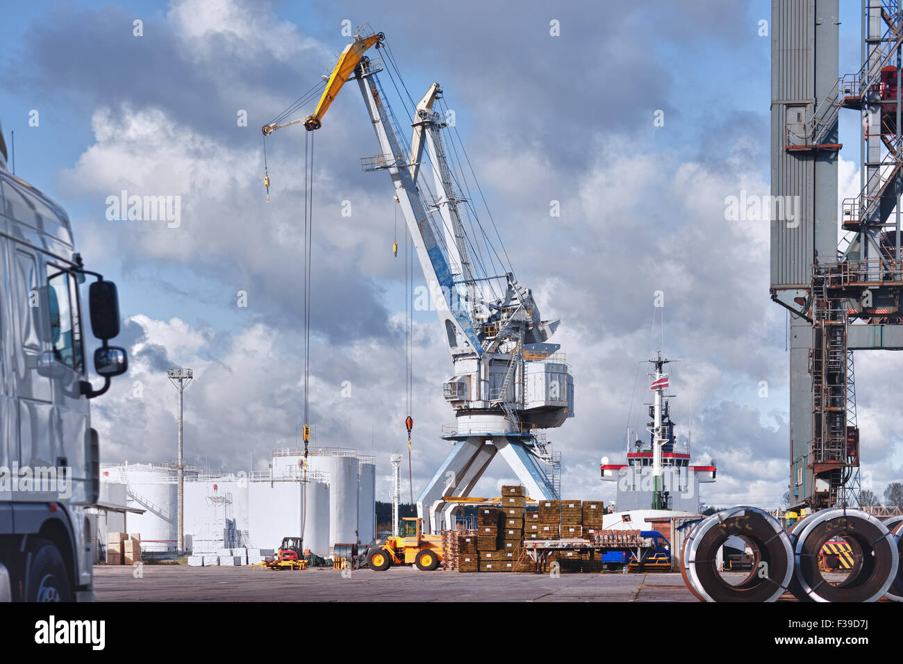 Cranes and ships in the port of the machines and forklifts for loading and unloading on a sunny summer day - Stock Image