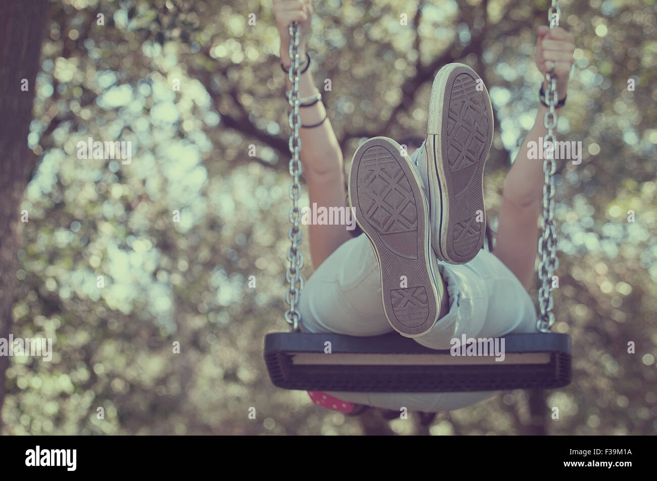 Low angle view of a teenage girl on a swing - Stock Image