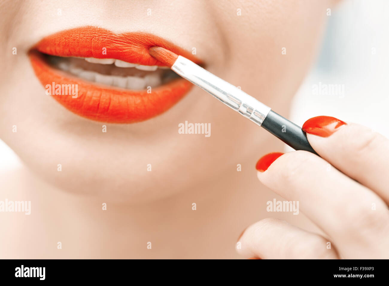 Woman applying red lipstick. Close-up view on face - Stock Image