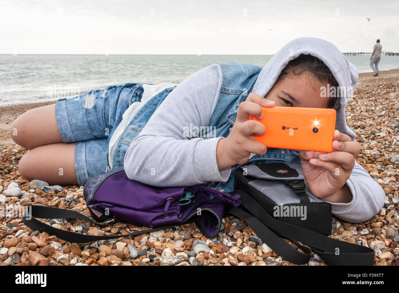 Teenage girl takes photo with flash using mobile phone. Stock Photo