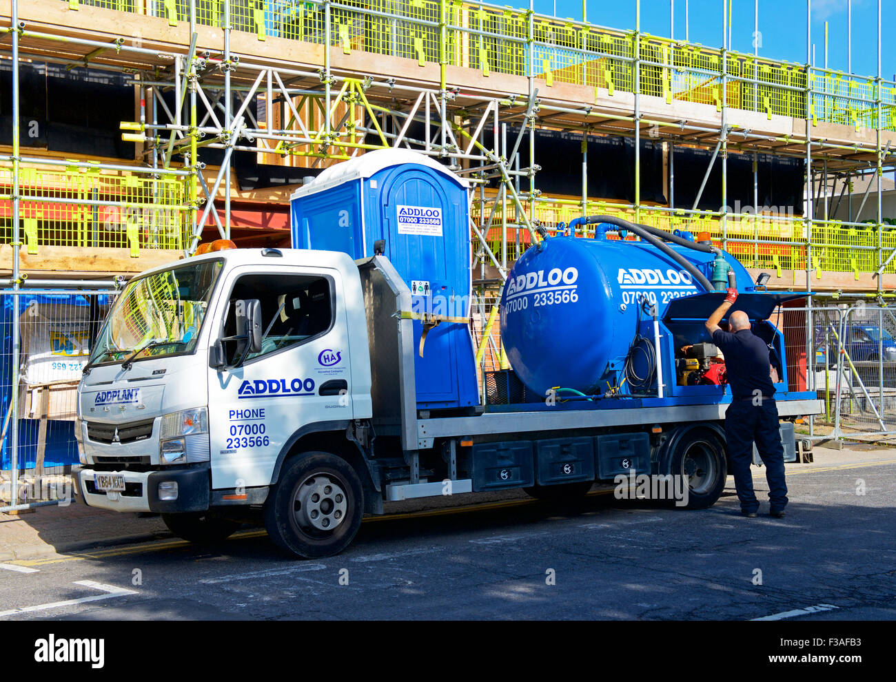 Lorry delivering portable toilet to building site, England UK Stock Photo