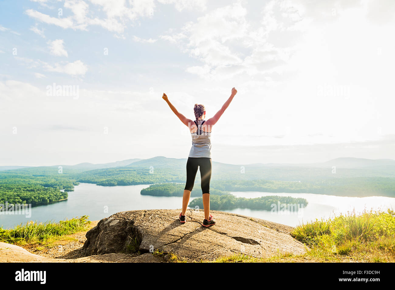 young woman standing on top of mountain with outstretched arms rear