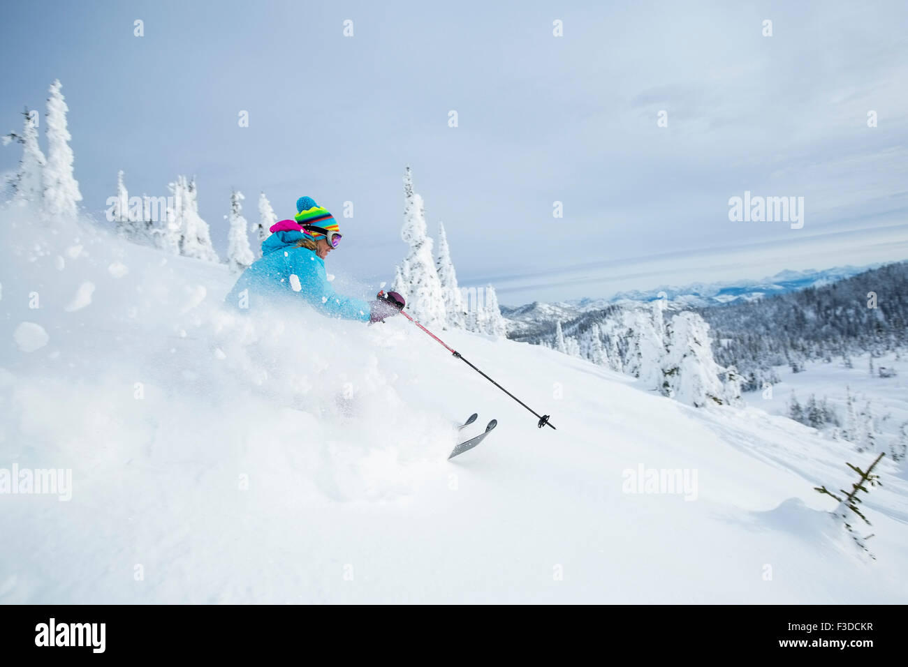 Mature woman speeding on ski slope - Stock Image