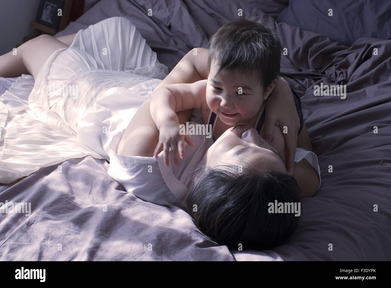 Mother and baby boy relaxing on bed together - Stock Image