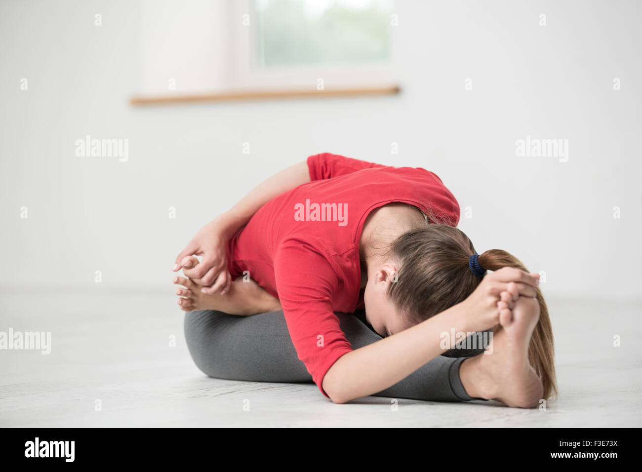 Portrait of a young woman doing stretching exercises in gym - Stock Image