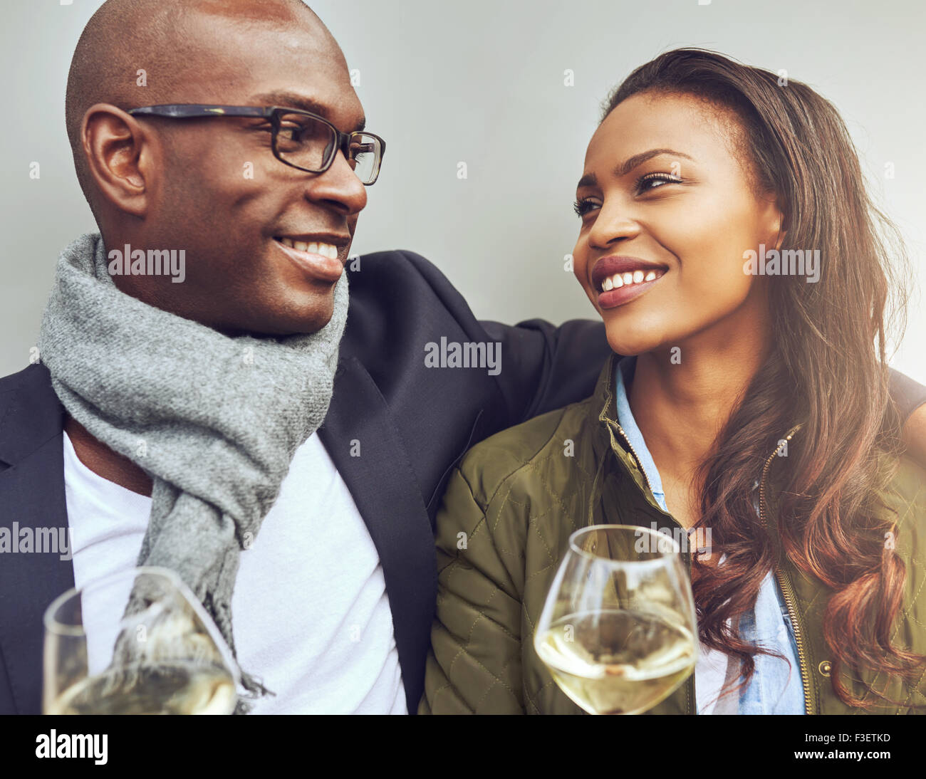 Romantic young African American couple sitting arm in arm enjoying glasses of white wine and smiling lovingly into - Stock Image