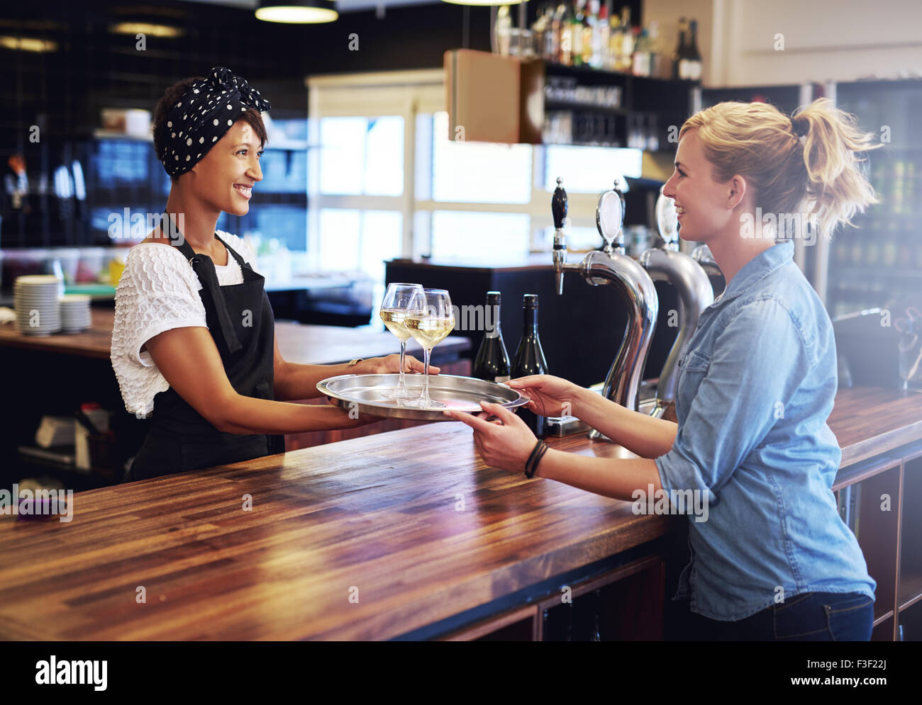 Smiling Waitress Giving Glasses of Wines on a Tray to a Female Customer at the Bar Counter. - Stock Image