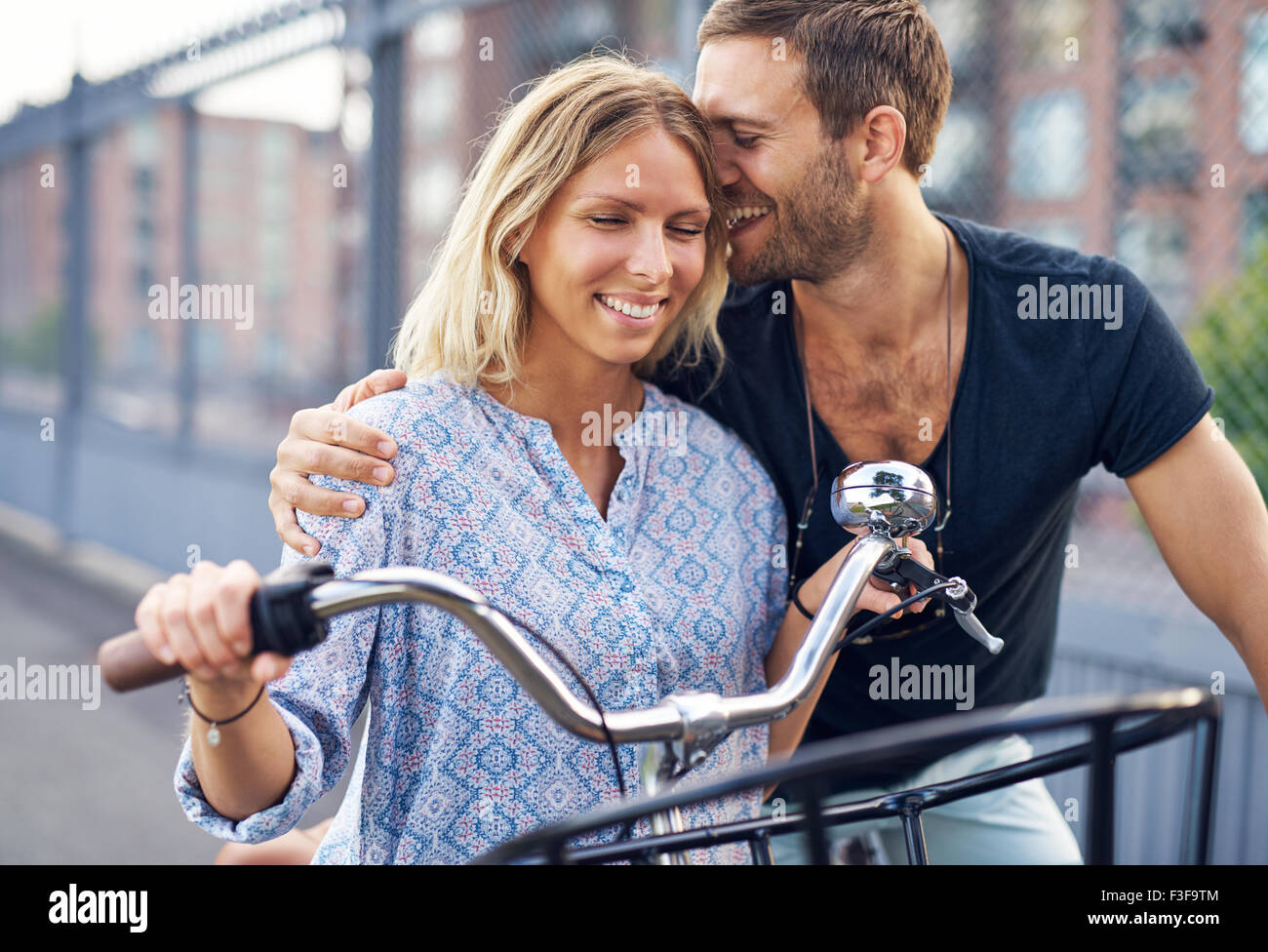 City couple loving each other while out riding bikes - Stock Image