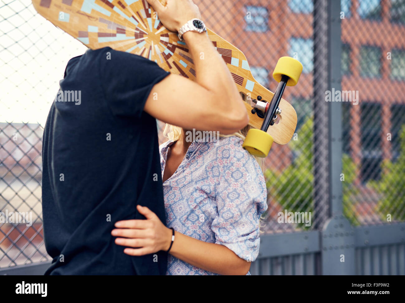 caressing couple hiding behind skateboard and kissing - Stock Image