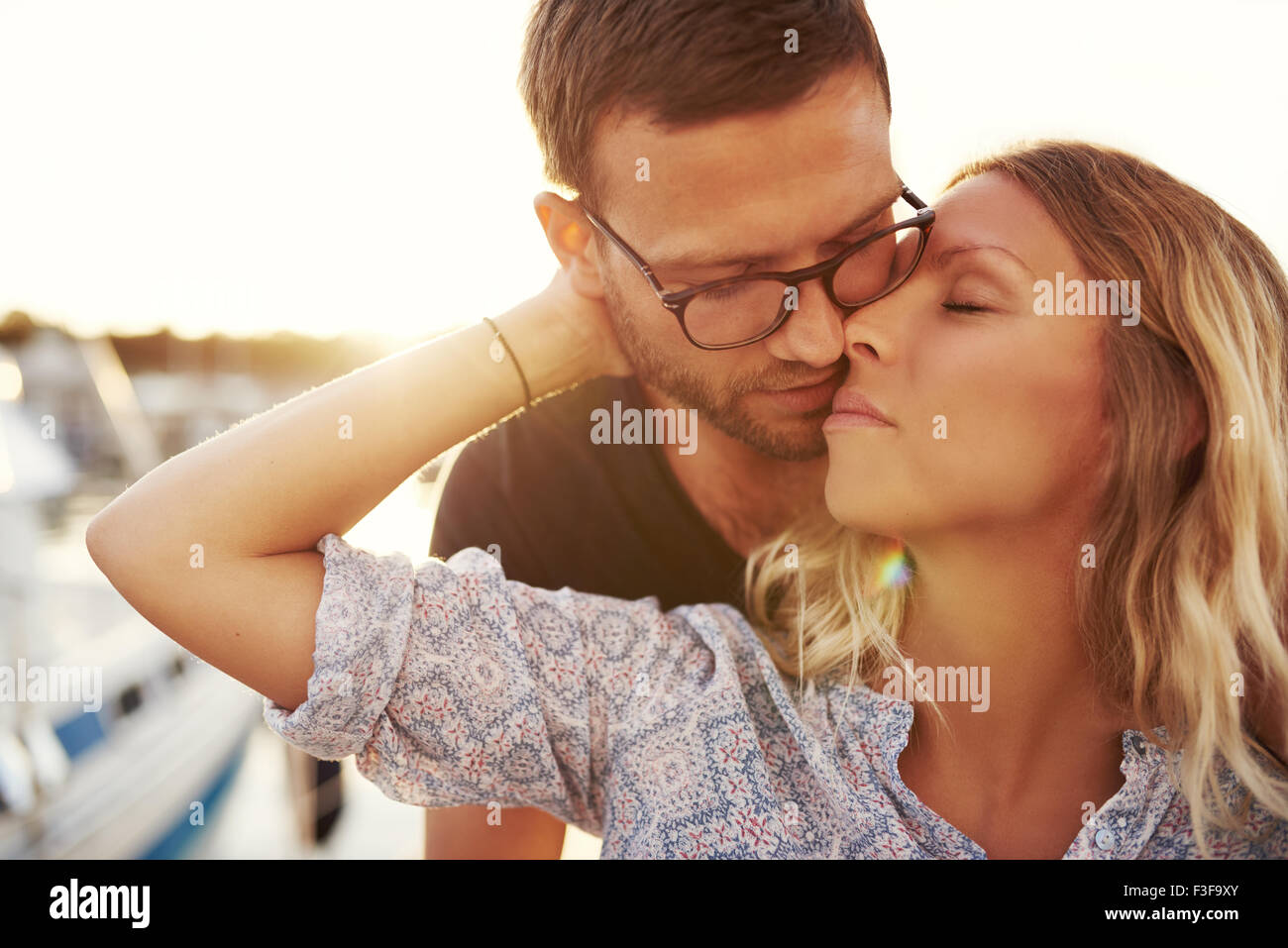 Couple Kissing On A Summer Evening, Blonde Woman and Man with Glasses - Stock Image