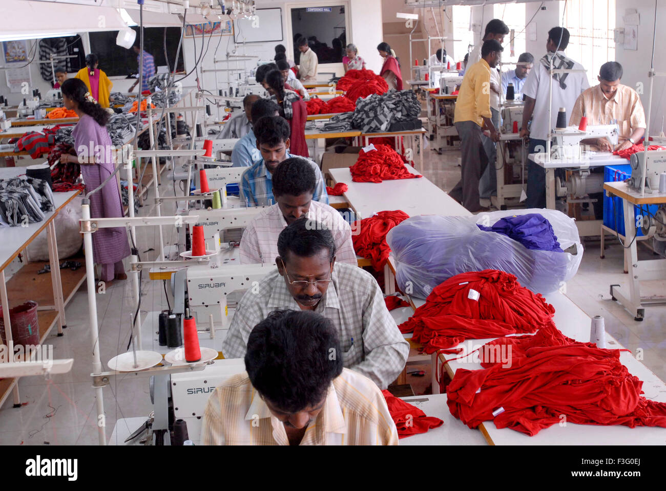 Stitching in a garment industry ; Tirupur ; Tamil Nadu ; India - Stock Image