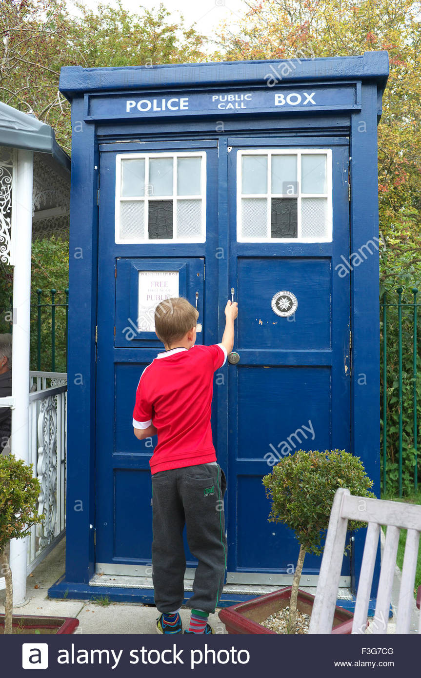A young lad enters a police phone box, which is now used as a toilet (the Tardis toilet), at Warmley Waiting Room Stock Photo