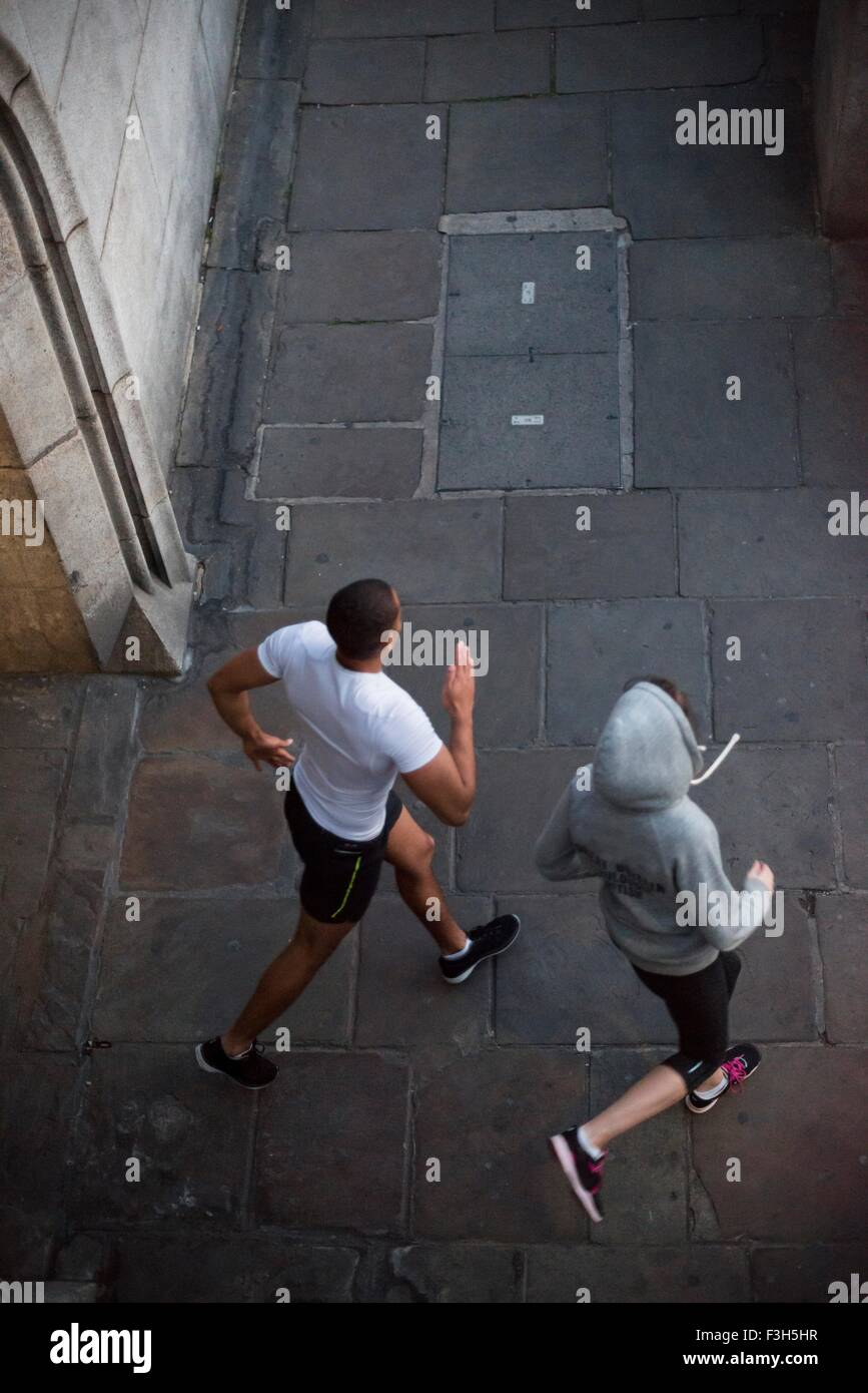 Overhead view of male and female runners running in city - Stock Image