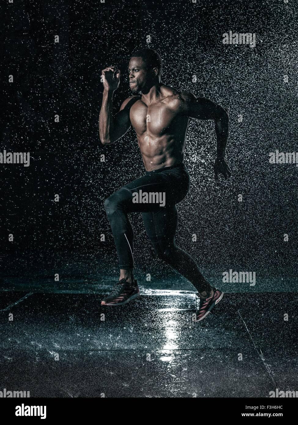 MId adult man, outdoors, running in rain - Stock Image