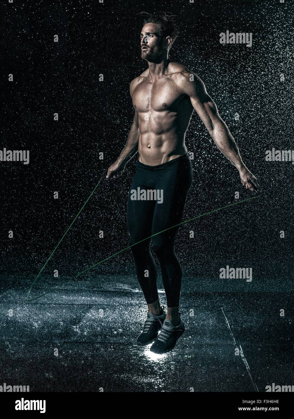 MId adult man, outdoors, skipping in rain - Stock Image