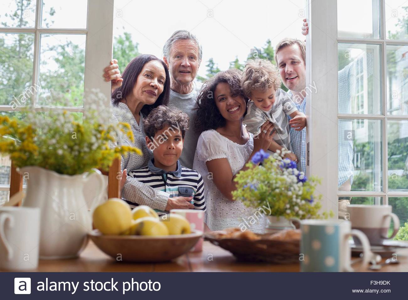 Portrait of family standing at patio doors, ready for breakfast - Stock Image