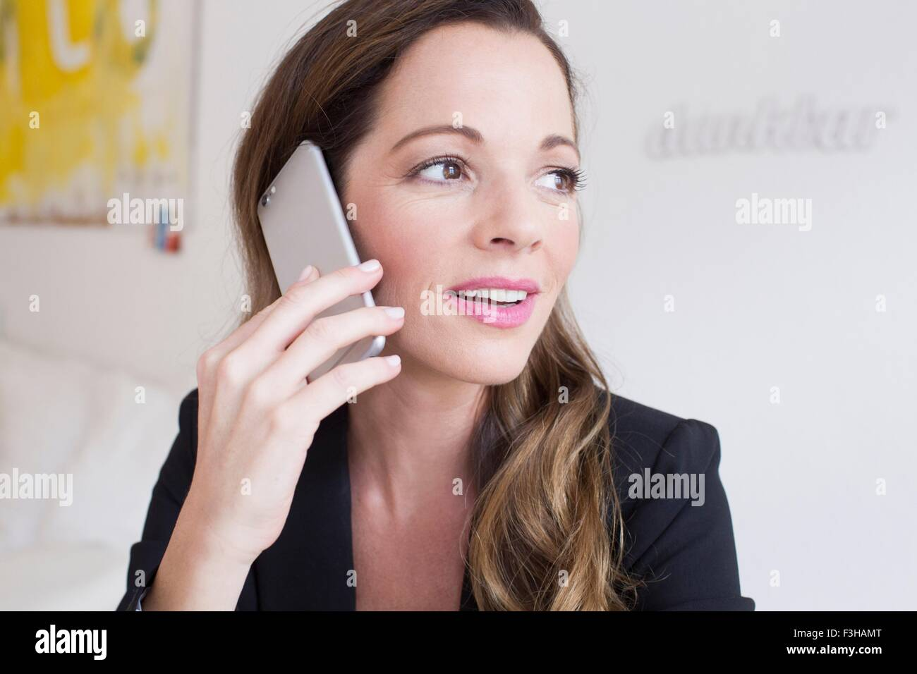 Head and shoulders of mature woman using smartphone looking away - Stock Image