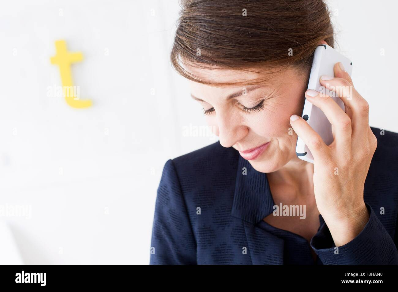 Head and shoulders of mature woman using smartphone, looking down smiling - Stock Image