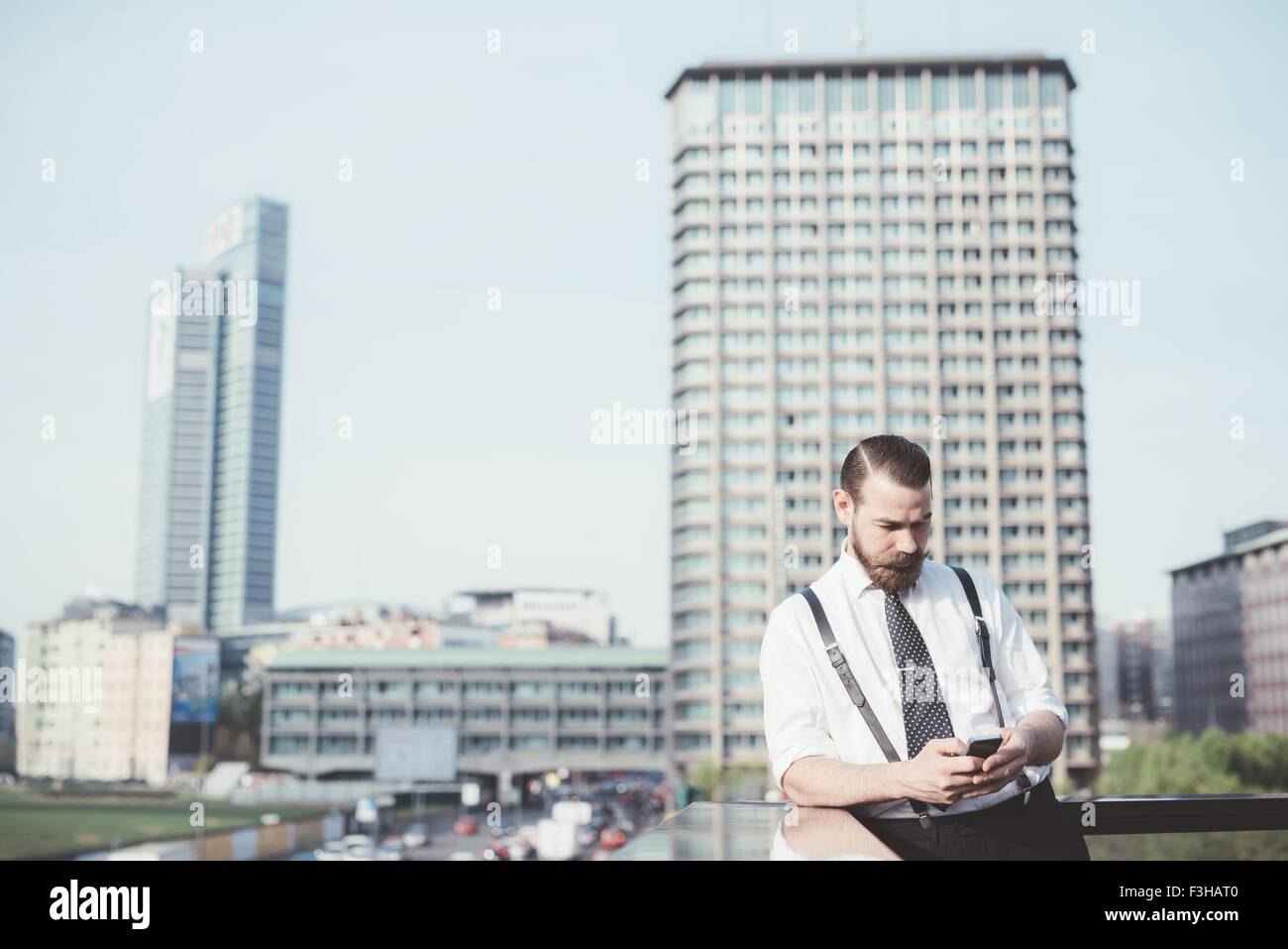 Stylish businessman reading smartphone text update on office balcony - Stock Image