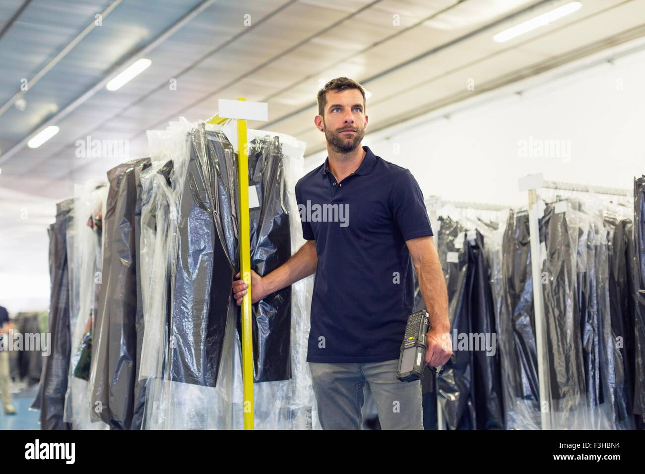 Warehouse worker pulling garment clothes rail in distribution warehouse - Stock Image