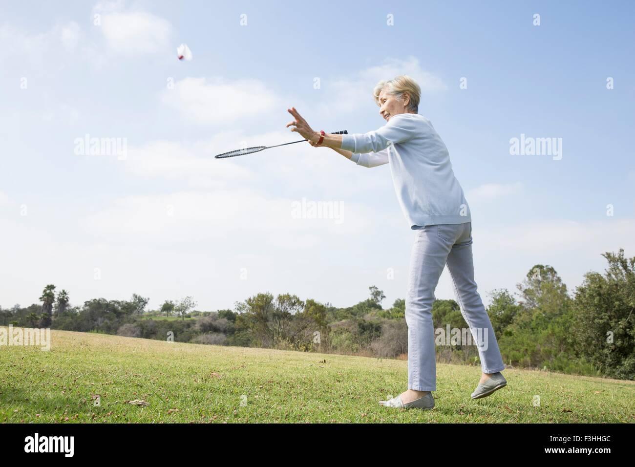 Senior woman playing badminton in park - Stock Image