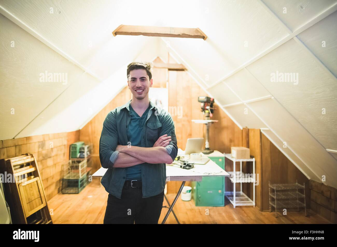 Young man standing in workspace, arms folded, looking at camera smiling - Stock Image