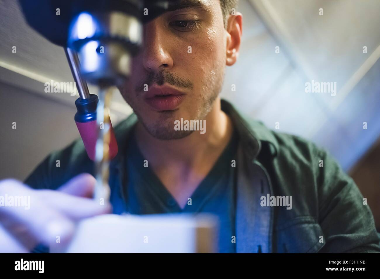 Low angle view of young man using tool, face partially obscured - Stock Image