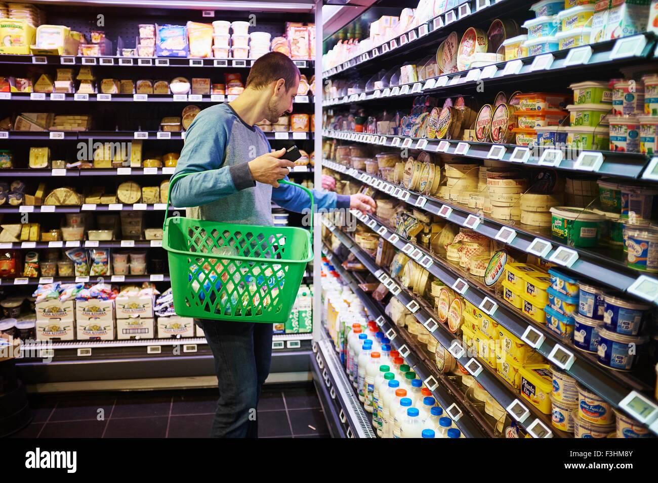 Man shopping in supermarket - Stock Image