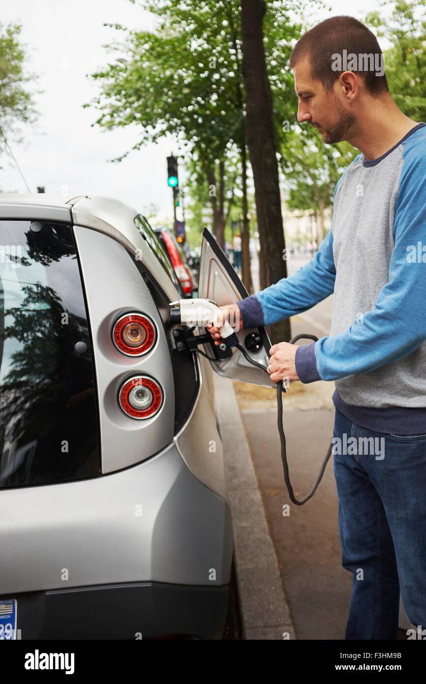 Man charging electric car on street, Paris, France - Stock Image