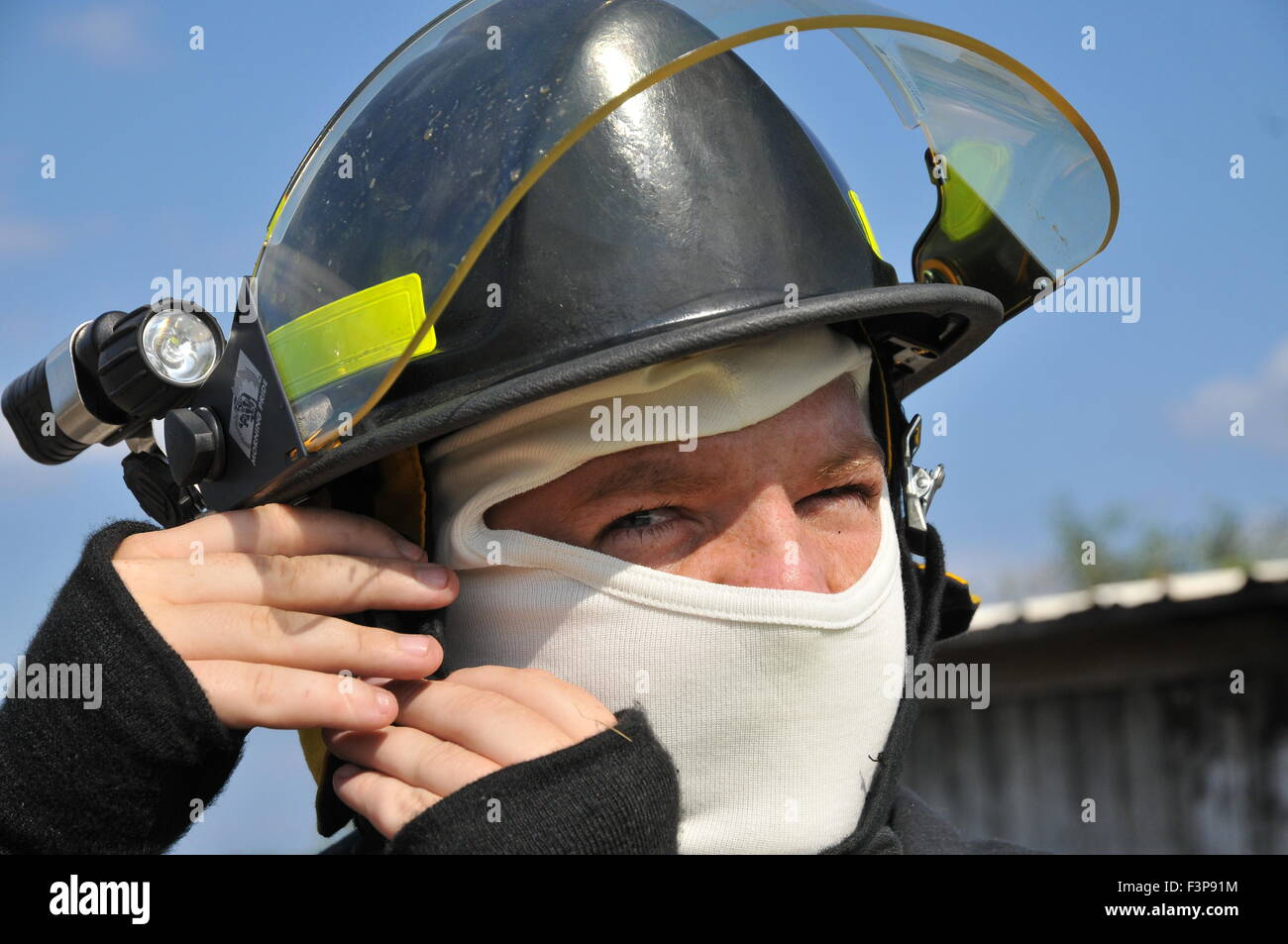 Portrait of a fire fighter in fire resistant clothes - Stock Image