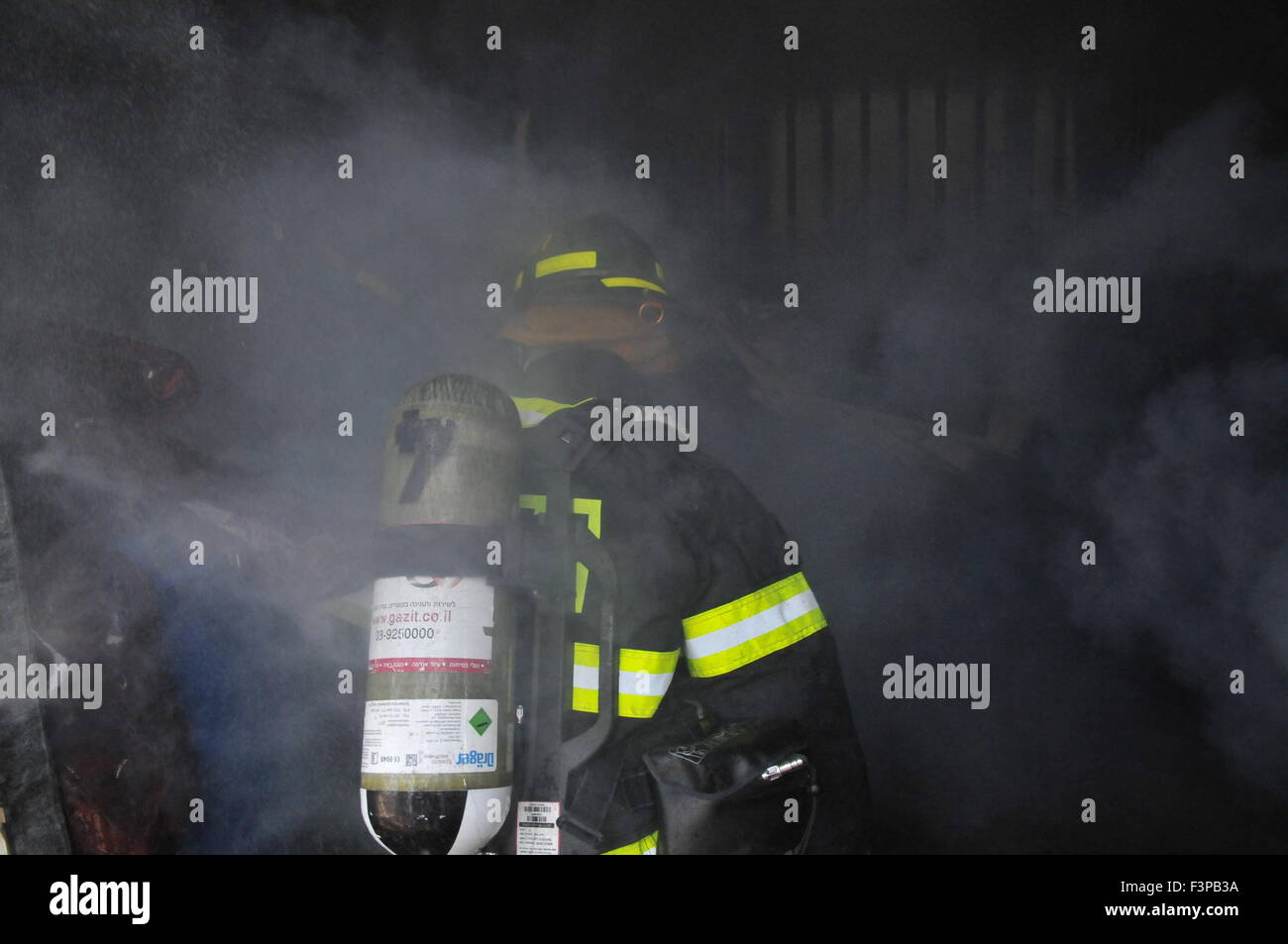 Firefighters with protective equipment in a smoke filled room - Stock Image