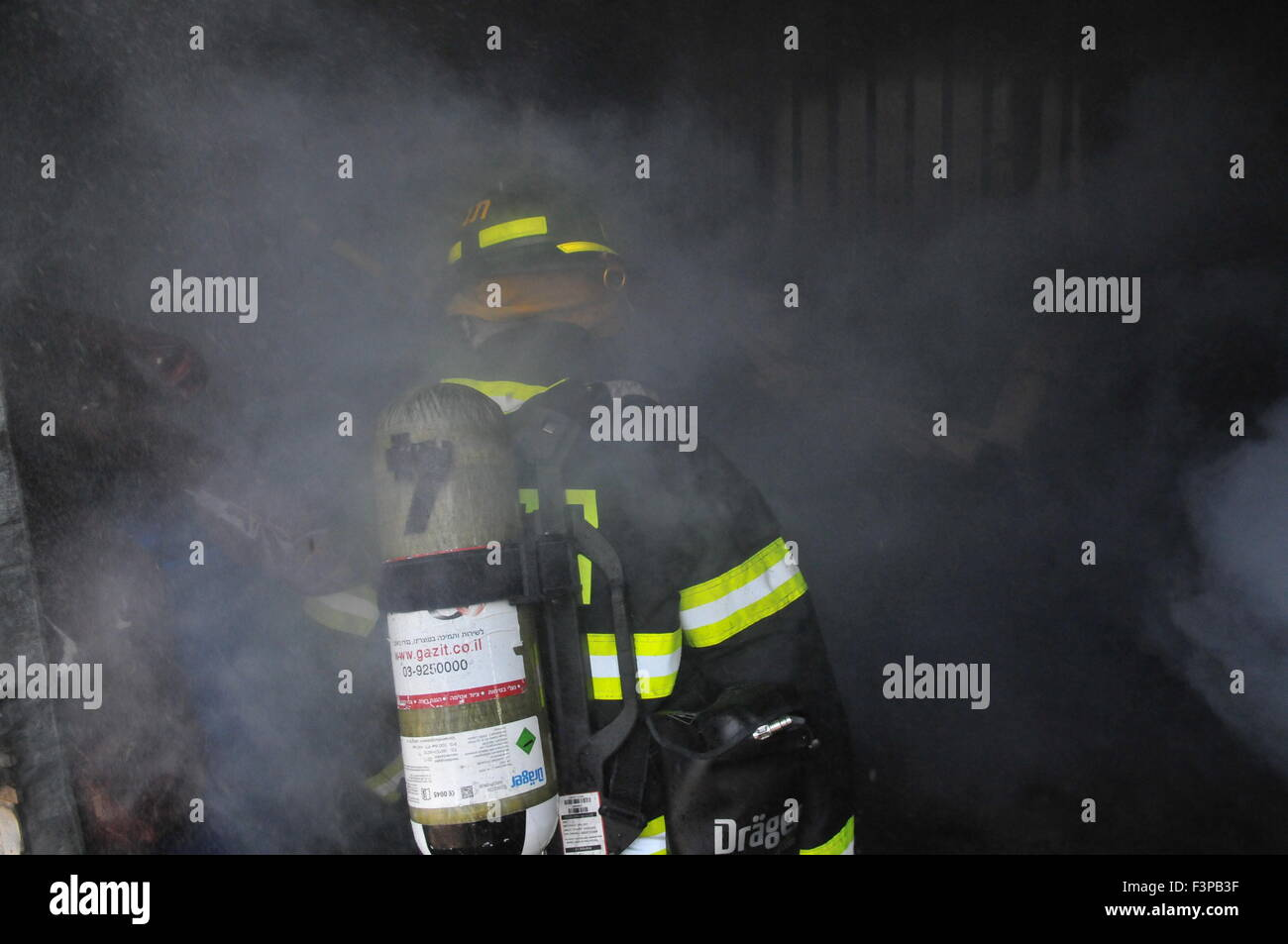 Firefighters with protective equipment enter a smoke filled room - Stock Image