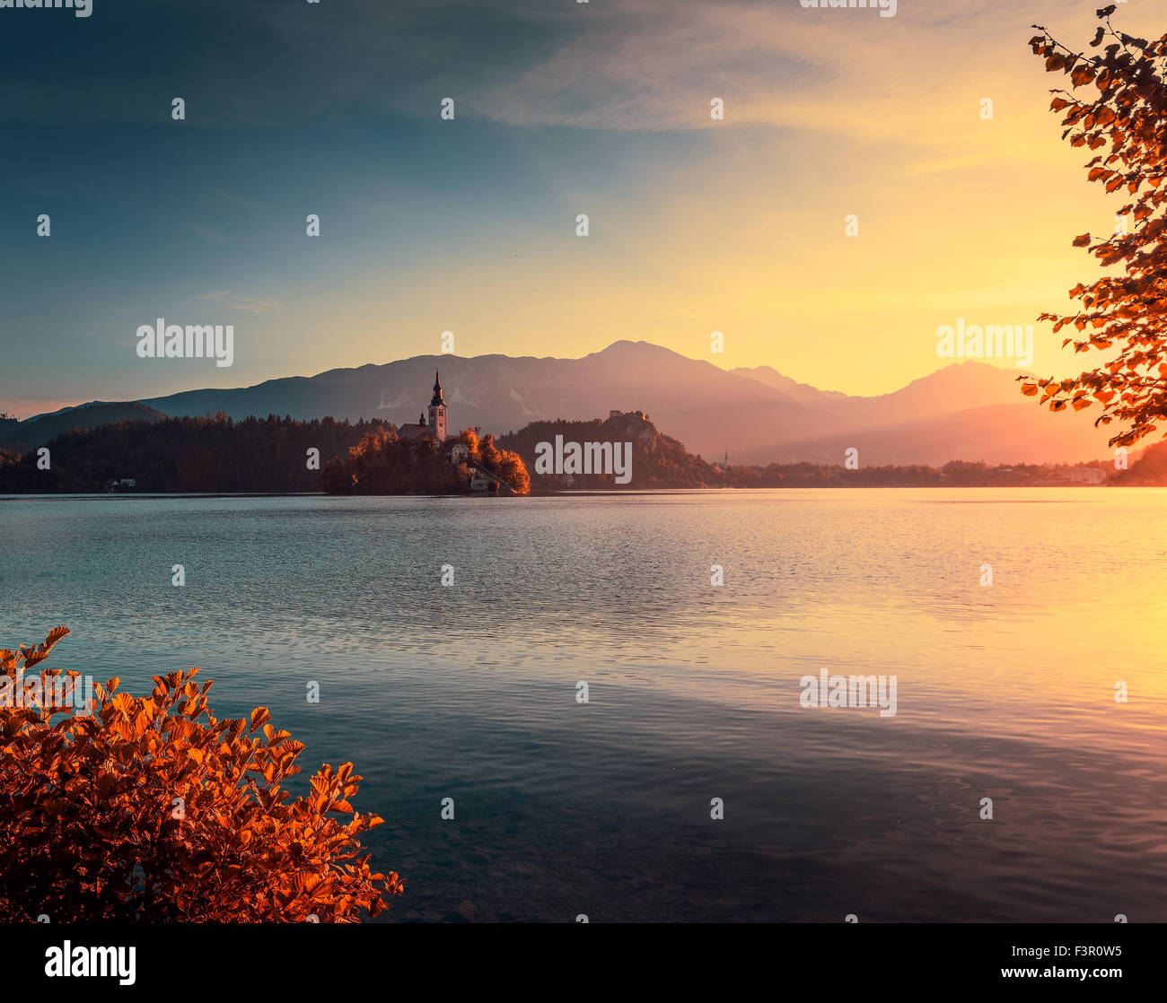 Famous Catholic Church on Little Island in Bled Lake, Slovenia at Autumn Sunrise with Mountains in BackgroundStock Photo