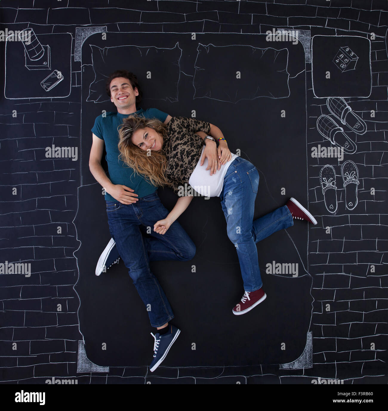 Young couple feeling joyful in bed. Image taken from above. - Stock Image