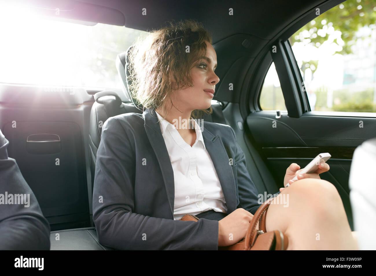 Young businesswoman traveling to work in the luxury car on the back seat holding mobile phone and looking outside - Stock Image