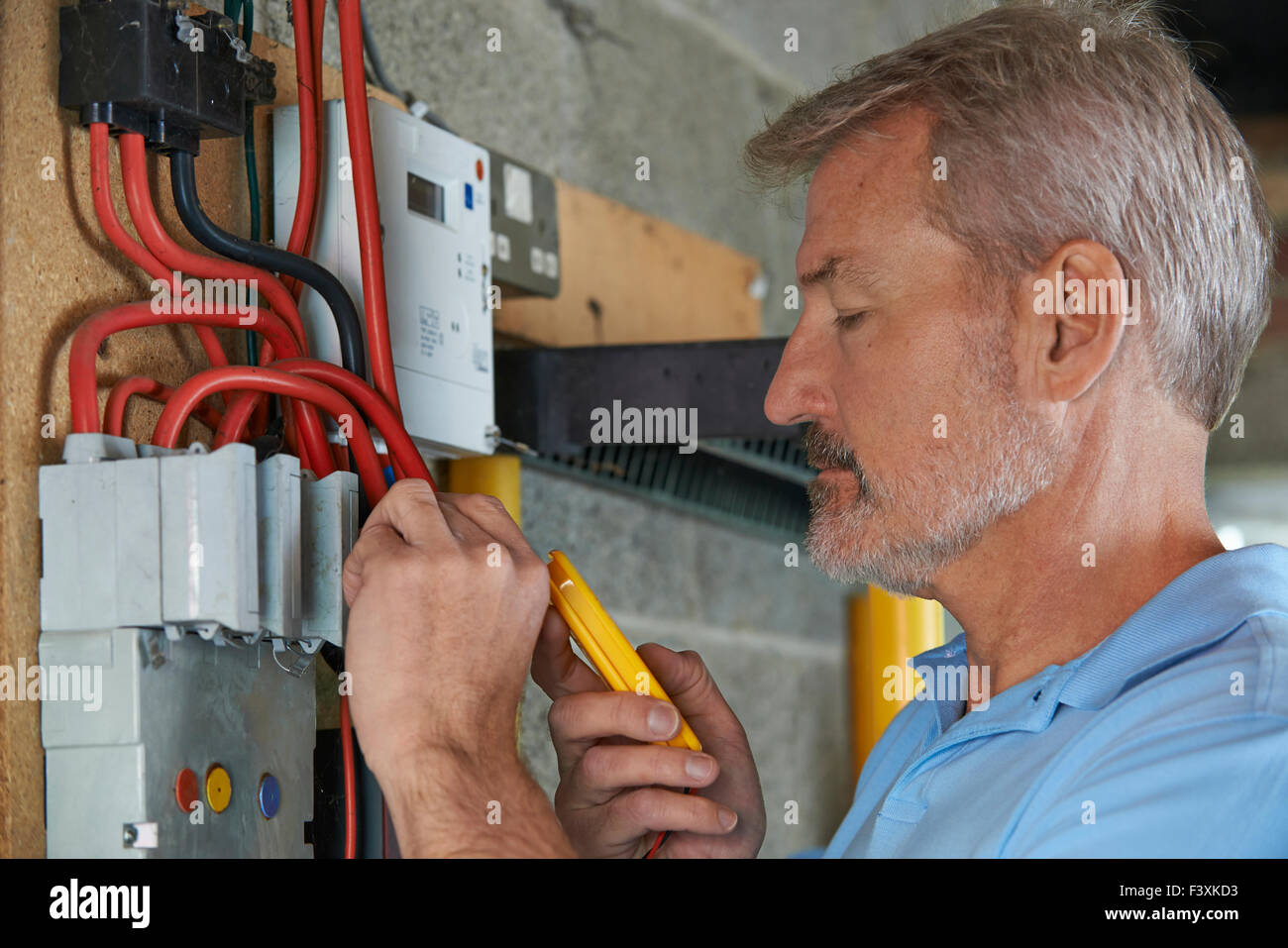 Electrician Testing Power Supply At Fuse board - Stock Image