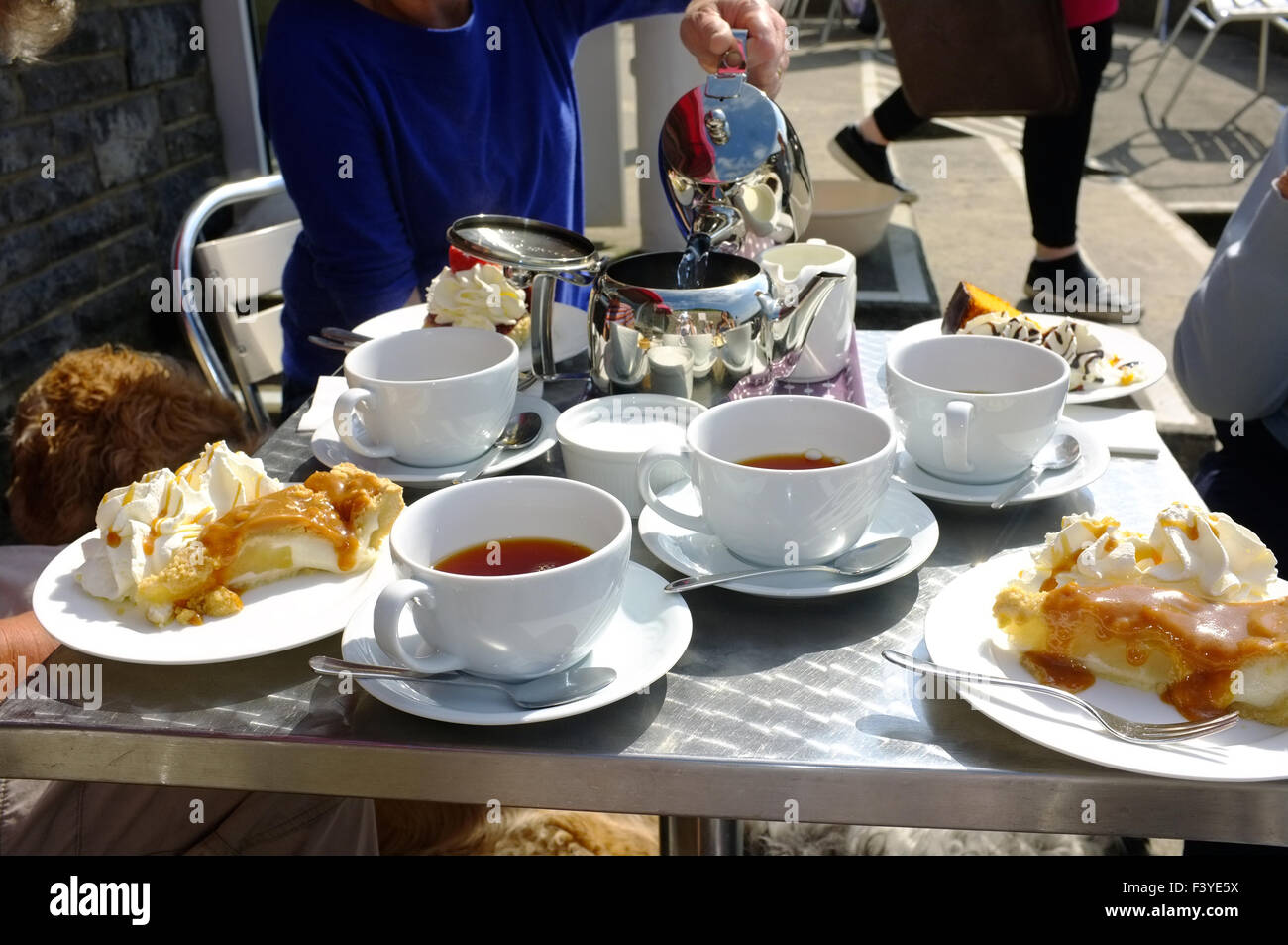 A table full of cups of tea and plates of cake for afternoon tea at a seaside cafe serving afternoon tea in Wales & A table full of cups of tea and plates of cake for afternoon tea at ...