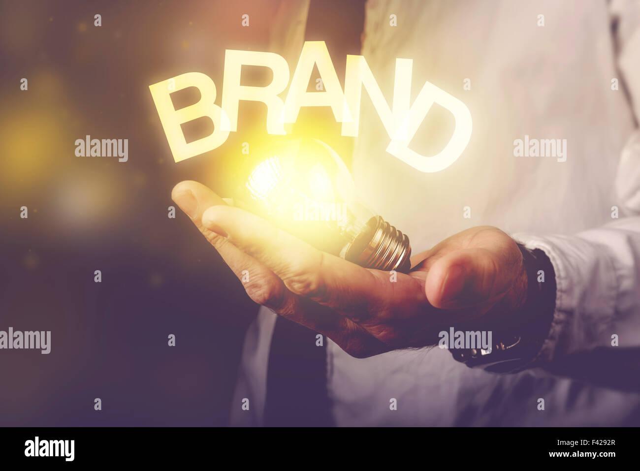 Brand idea concept with businessman holding light bulb, retro toned image, selective focus. - Stock Image