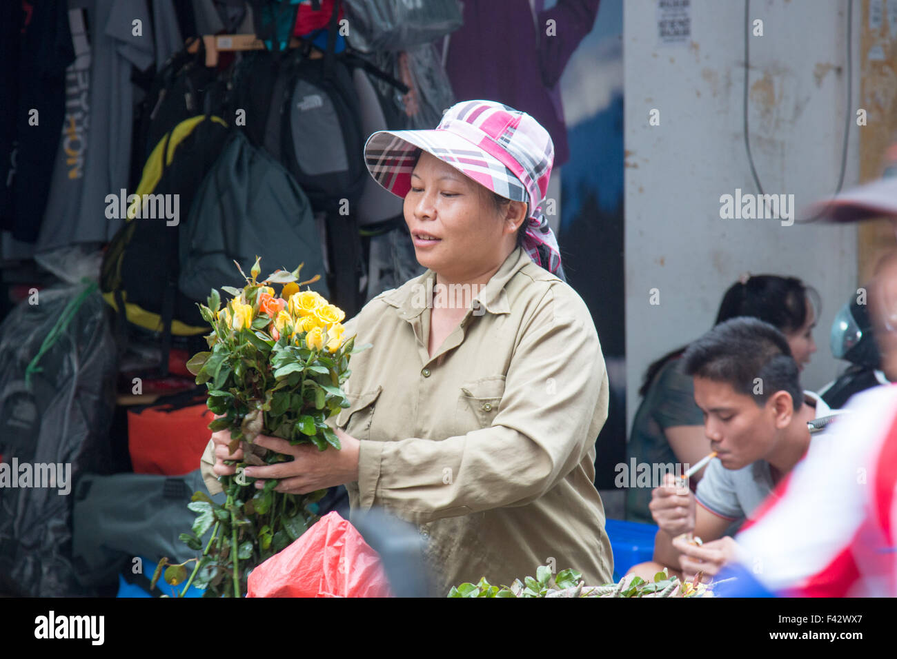 vietnamese street flower seller handing bunch of flowers to a purchaser,Hanoi,Vietnam - Stock Image