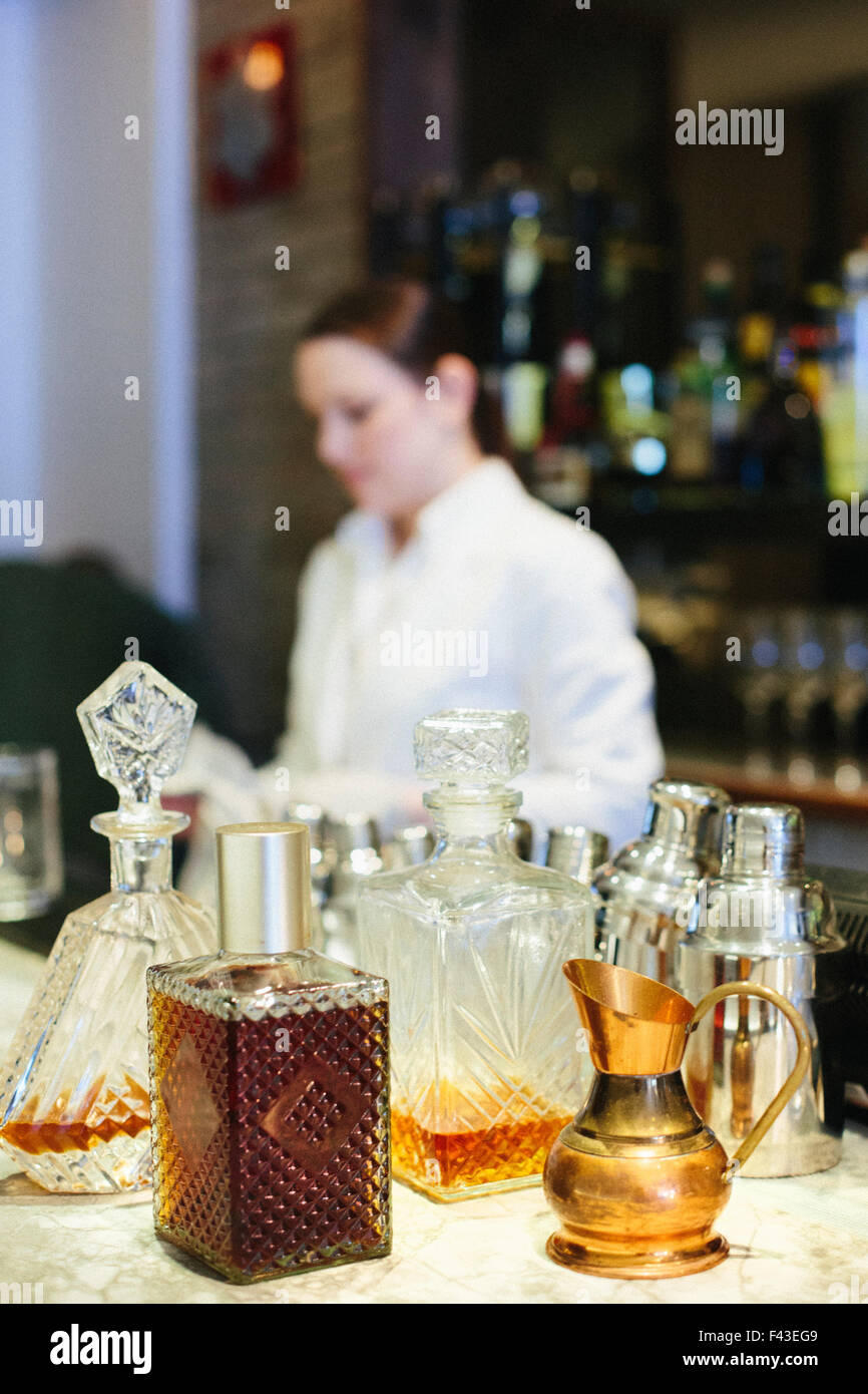 Young woman mixing a cocktail at a bar in a city restaurant. - Stock Image