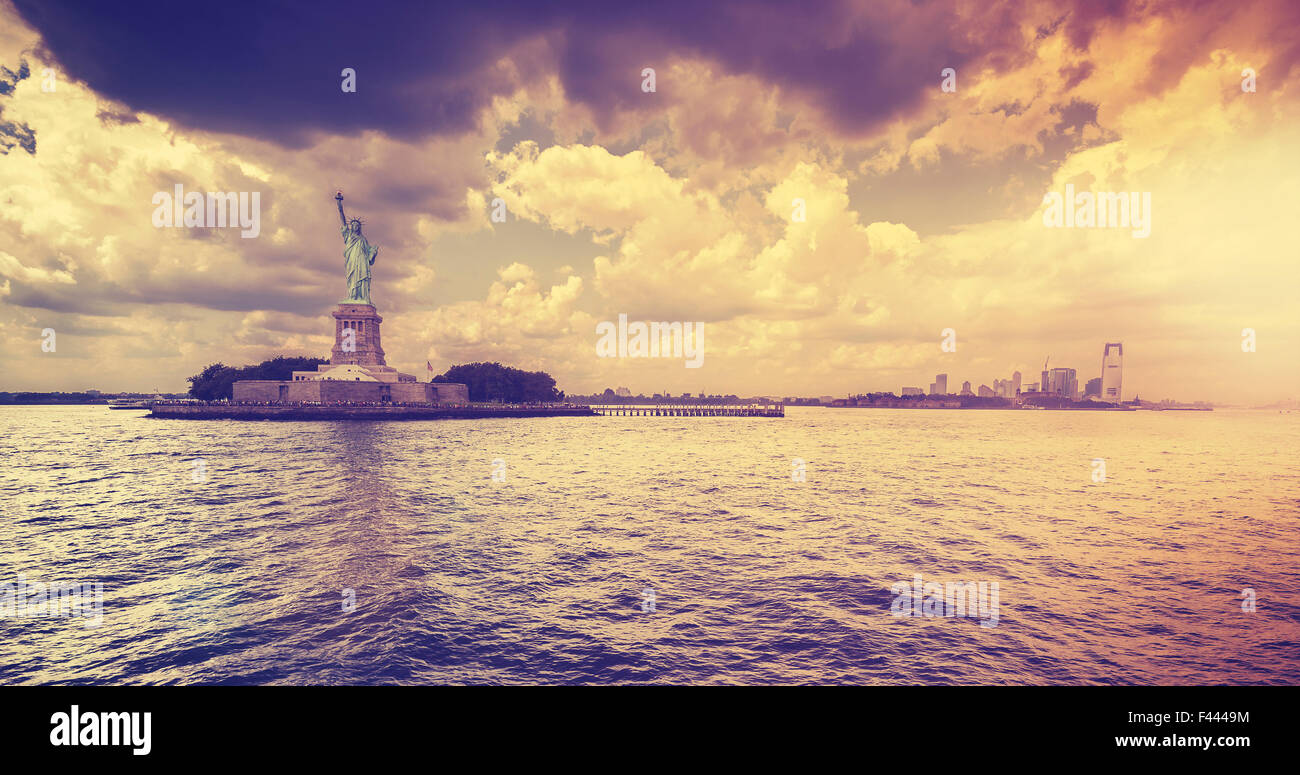 Vintage style Statue of Liberty with dramatic sunset, New York, USA. - Stock Image