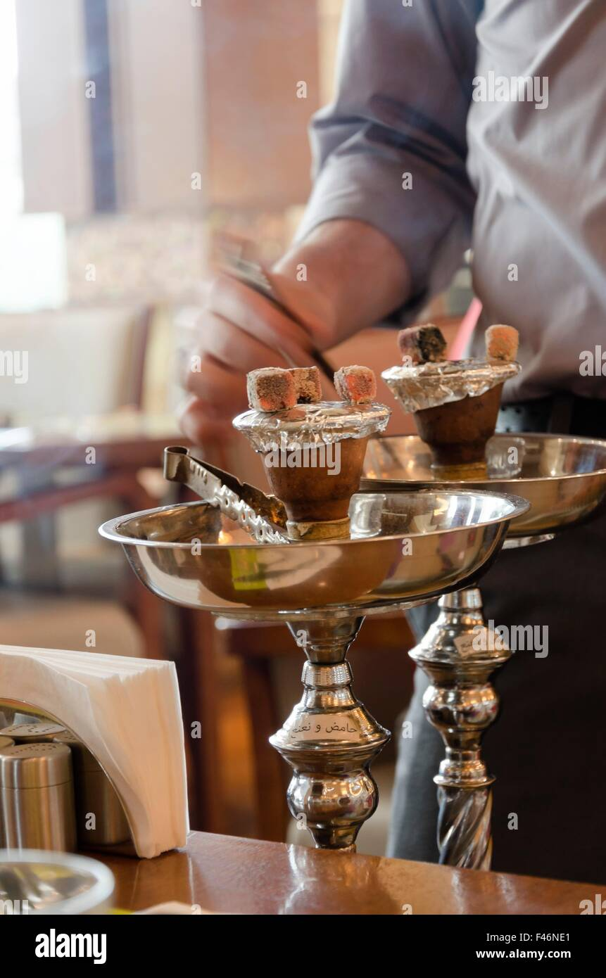 Preparing the shisha, aka nargile or hookah at a restaurant by placing the charcoals on top. A very middle eastern - Stock Image