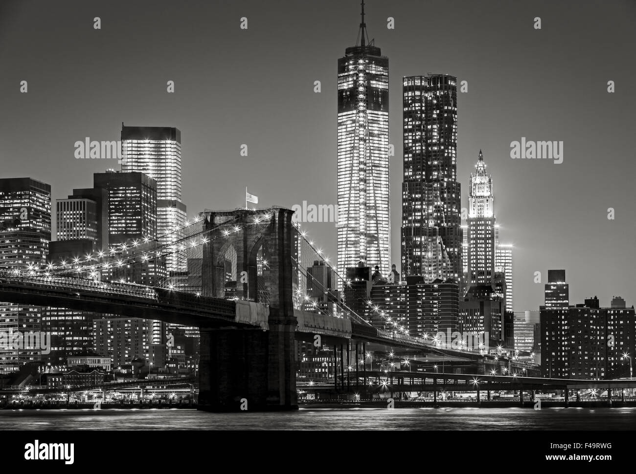 Black & White cityscape by night. View of Brooklyn Bridge, Lower Manhattan and  Financial District's skyscrapers, - Stock Image
