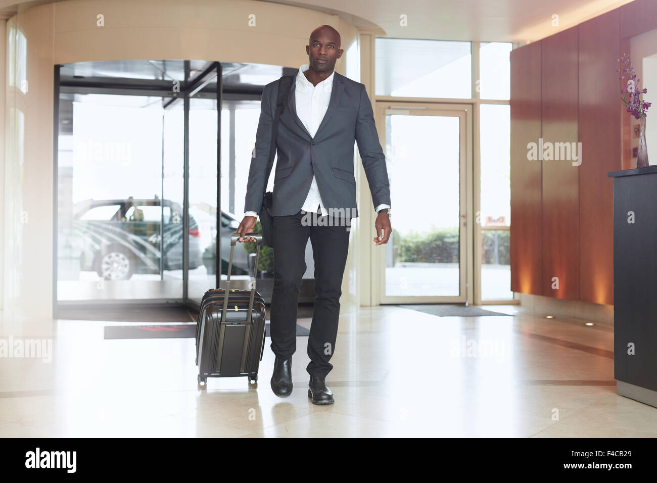 Businessman walking in hotel lobby. Full length portrait of young african executive with a suitcase. - Stock Image