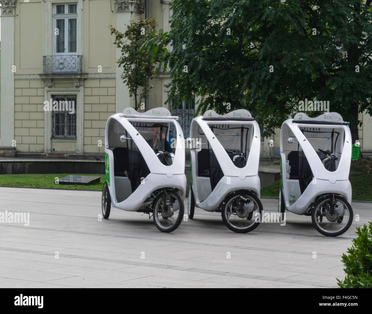 Three Eco Taxis waiting for customers Krakow Poland environmentally friendly pollution free transport in this popular - Stock Image
